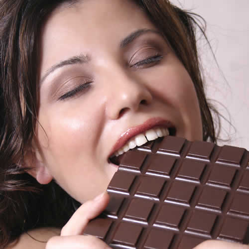 Woman eating chocolate instead of blogging